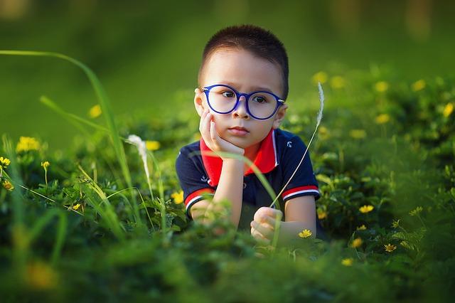 brýlatý kluk v trávě