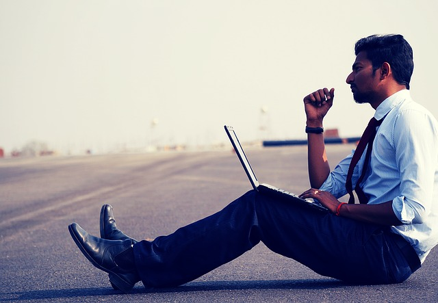muž sedící s notebookem na silnici
