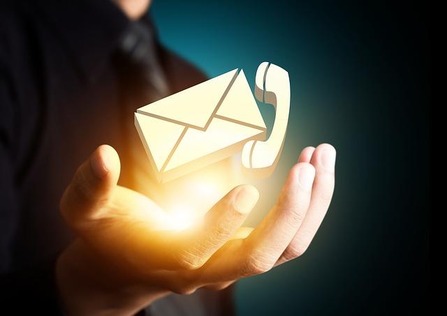 muž, který vztahuje ruku a na dlani má obálku a telefon – nabízí kontakt