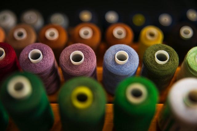 spousta cívek s barevnými nitěmi