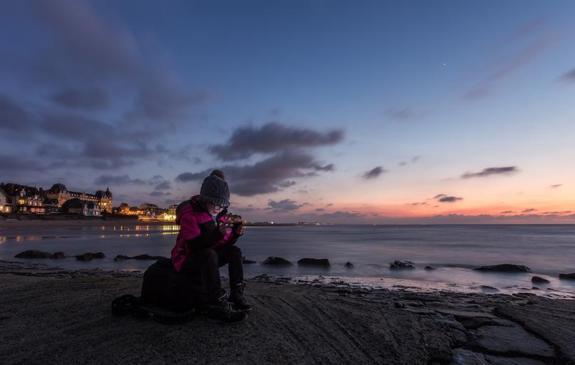 žena v bundě a čepici sedí na pláži u moře, je tma, za ní svítí město