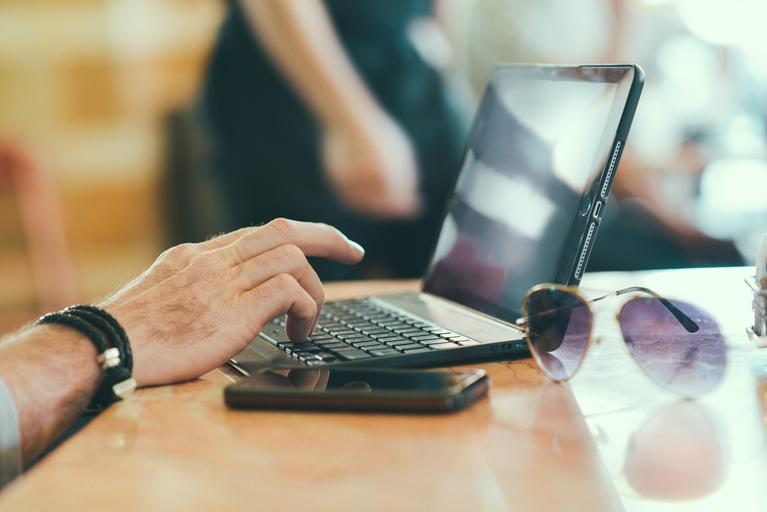 na stole je notebook, telefon, brýle, ruka jezdí po klávesnici, někde v restauraci