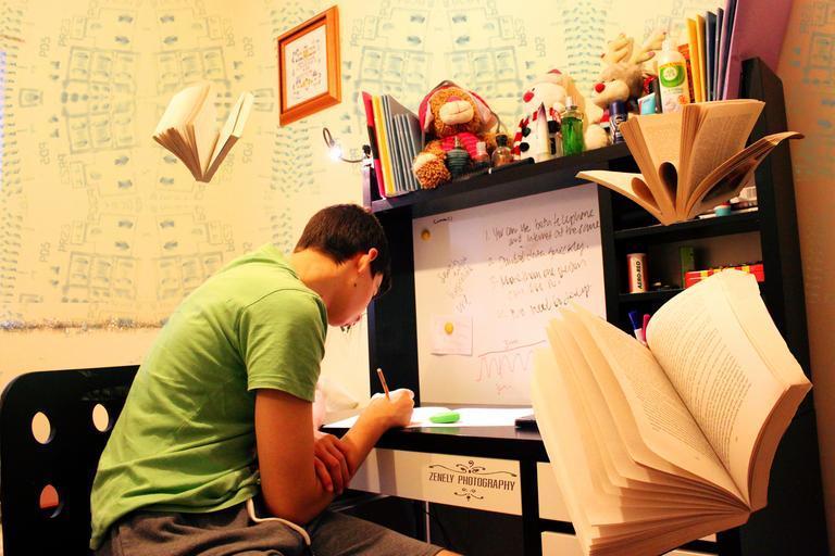 pokoj pro studenty – sedí u stolu a učí se
